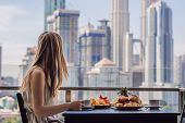 A Young Woman Is Having Breakfast On The Balcony. Breakfast Table With Coffee Fruit And Bread Croisa poster