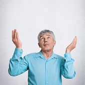 Vertical Shot Of Attractive Grey Haired Mature Elderly Male Prays And Asks God For Something Desirab poster