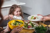 Eat, My Baby. Portrait Of Excited Little Girl Is Eating Salad While Sitting At Table Near Parents. F poster
