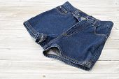Womans Vintage Denim Shorts On Wooden Shelf poster
