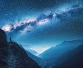 Milky Way, Girl And Mountains. Silhouette Of Standing Woman On The Mountain Peak, Mountains And Star poster