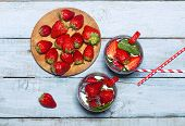 Summer Cold Drink With Strawberries, Mint And Ice In Glass On Blue Wooden Background. poster