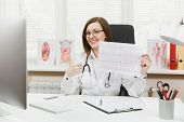 Young Female Doctor Sitting At Desk With Medical Documents, Electrocardiogram Record, Heart Ekg Card poster