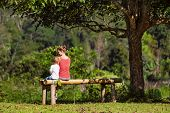 Mother, Little Baby Son Have Fun Outdoors, Sit On Bench Under The Tree On Sunny Lawn. Happy Family L poster
