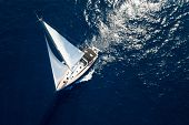Sailboat while cruising / sailing at opened sea. Yacht with full sails up at the end of windy day. S poster