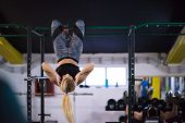 athlete woman doing abs exercises hanging upside down on horizontal bar at cross fitness gym poster