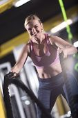 young fit athlete woman working out in functional training gym doing  battle ropes exercise as part  poster