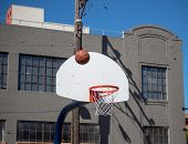 A Basketball Rebounding After A Missed Shot On An Outdoor Streetball Hoop poster