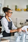 friendly african american shop assistant using pos terminal to input orders at restaurant            poster