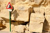 foto of landslide  - Landslide warning sign surrounded by fallen rocks - JPG
