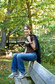 picture of tennis elbow  - Young attractive teen sits on the back of a park bench - JPG