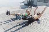 Fit Fitness Woman And Man Doing Fitness Exercises Outdoor At City Background. Couple Doing Hamstring poster