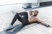 Fit Fitness Man Doing Fitness Exercises Outdoor At City Background. He Doing Hamstring Leg Exercise  poster
