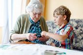 Active Little Preschool Kid Boy And Grand Grandmother Playing Card Game Together At Home. Little Chi poster