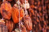 Dried Persimmon Suspended On A Rope, Air-drying Dried Fruits. poster