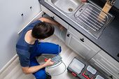 Male Plumber Cleaning Clogged Sink Pipe In Kitchen poster