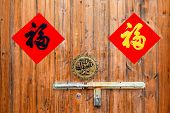 Two colorful Chinese blessing Fu  for Chinese new year on the  traditional chinese  wooden door wi poster