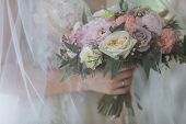 Wedding Bouquet Under The Veil. The Bride Is Holding A Bouquet. Elegant Wedding Bouquet Of Peonies.  poster