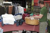 pic of yard sale  - Male holding a basket with linens inside at a yard sale in front of a table with a sleeping bag and clothing items - JPG