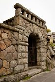 picture of entryway  - An arched stone entryway with keystone and wrought iron gate - JPG