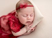 Cute newborn in red lace outfit resting on tiny pillow poster