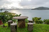 Stone Table With Indigenous Art Overlooking Lake Arenal In Costa Rica. Surrounded By Green Pasture A poster