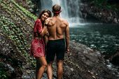 A Couple In Love On A Waterfall. A Beautiful Girl Embraces A Man Of Athletic Build At The Waterfall. poster