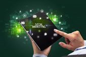Businessman holding a foldable smartphone with SOCIAL MARKETING inscription, social networking conce poster
