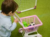 Boy With A Food Basket Toy. Shopping, Discount, Sale Concept. Cheerful Boy With A Shopping Cart And  poster