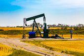 A Wide View Of A Pumpjack In Farmland. Finite Resource Mining. Gasoline, Oil, Petroleum, Diesel, Gas poster