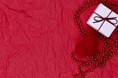 Valentin Day Background. On A Red Background On The Right There Is A Knitted Red Heart, Red Beads An poster