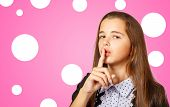 Beautiful Brunette Teen Girl With Long Hair Gestures Quietly On Pink Background poster