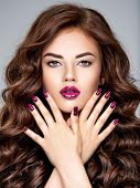 Beautiful and stunning woman with bright purple lipstick on lips and fingernails.  Young caucasian g poster