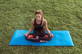Beautiful Girl Training In City, Meditating While Sitting Yoga Mat. Fitness Training Active Lifestyl poster