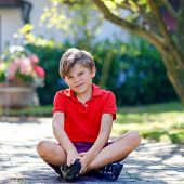 Portrait Of Little Cool Kid Boy Sitting On Ground On Sunny Day In Domestic Backyard. Happy Healthy C poster
