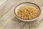 foto of flux  - gold flux seeds in a small ceramic bowl against a grunge wood surface - JPG