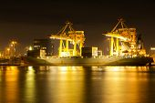 stock photo of loading dock  - Industrial Container Cargo freight ship with working crane bridge in shipyard at dusk for Logistic Import Export background - JPG