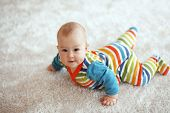 picture of overalls  - 6 months baby lying down on a soft cozy carpet and looking at camera - JPG