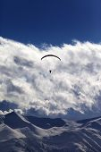 Winter Mountains With Clouds And Silhouette Of Parachutist
