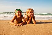 picture of kiddie  - Two happy children on beach lying on the beach - JPG