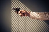 image of blind man  - Man is pointing a revolver at a window with shaows from the blinds - JPG