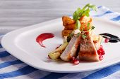 stock photo of marrow  - Grilled meat  with fried potato and marrow pieces and pomegranate seeds on plate - JPG