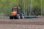 stock photo of plowed field  - Tractor plowing the field in the spring - JPG