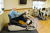 stock photo of physical exercise  - Elderly male physical therapy patient in a physical therapy rehab gym facility exercising on a recumbent stepper - JPG