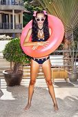 stock photo of flesh air  - Young woman in white sunglasses with pink inner tube standing at tropical resort in summer day - JPG