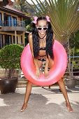 picture of flesh air  - Young woman in white sunglasses with pink inner tube looking at camera - JPG