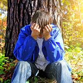 stock photo of sorrow  - Sorrowful Teenager sitting in the Forest alone - JPG