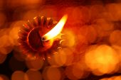 image of diwali lamp  - A unique traditional Diwali lamp image with an abstract view of a lit lamp through a line of blur lights