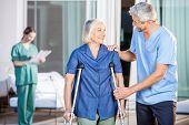 picture of male nurses  - Happy male caretaker helping senior woman in walking with nurse in background at nursing home yard - JPG