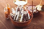 stock photo of vedic  - Little bottles with spices in a wooden bowl in the kitchen - JPG